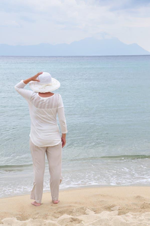 Vrouw die zich op het zandige strand bevinden stock foto's