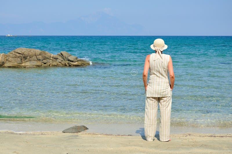 Vrouw die zich op het zandige strand bevinden stock afbeeldingen