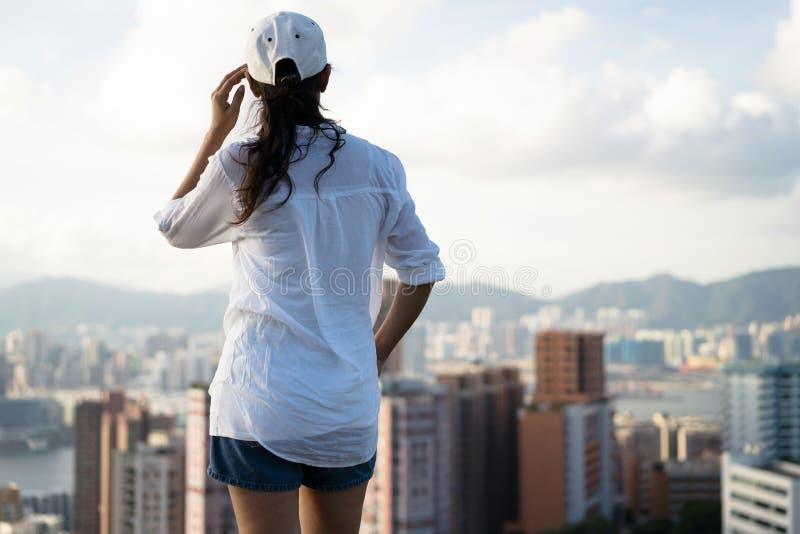 Vrouw die zich op moutain over het kijken bevinden de stad royalty-vrije stock foto's