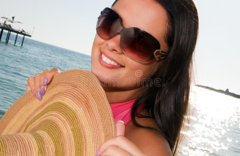 Vrouw die zich op oever bij het strand bevindt stock foto's