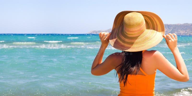 Vrouw die zich op oever bij het strand bevindt stock afbeelding