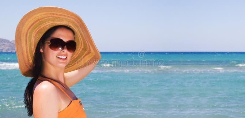 Vrouw die zich op oever bij het strand bevindt stock fotografie
