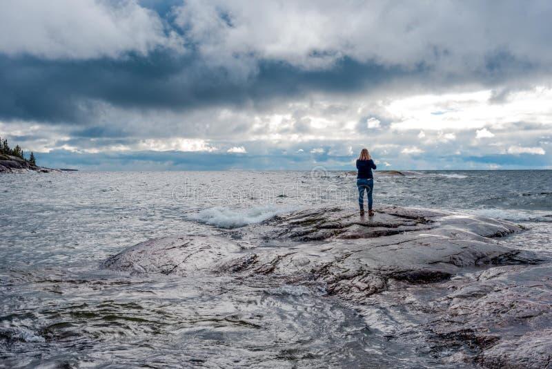 Vrouw die zich op rotsachtige kust met golven het verpletteren bevinden royalty-vrije stock fotografie