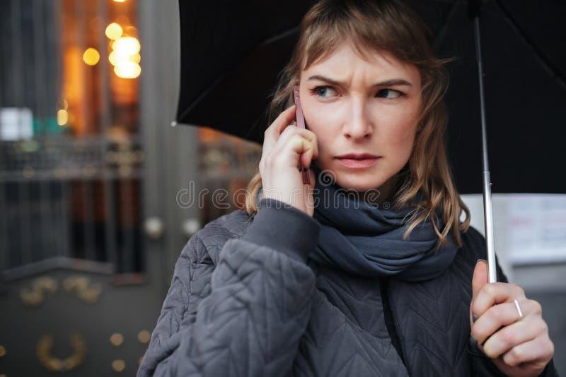 Vrouw die zich op straat met zwarte paraplu bevinden en op cellphone spreken terwijl ernstig opzij het kijken stock afbeeldingen
