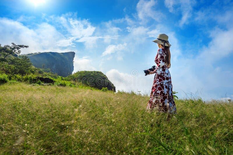 Vrouw die zich op weide bevinden en camera houden bij Phu-Chifa bergen in Chiangrai, Thailand reis concept stock afbeeldingen
