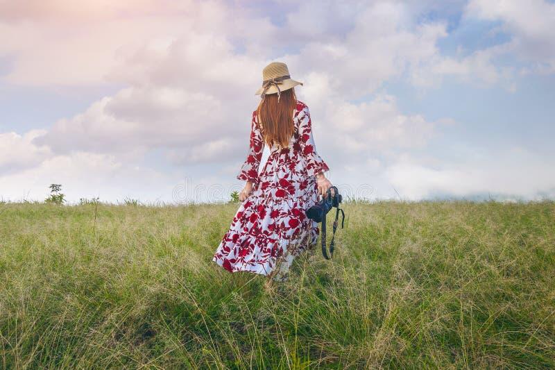 Vrouw die zich op weide bevinden en camera houden reis concept royalty-vrije stock fotografie