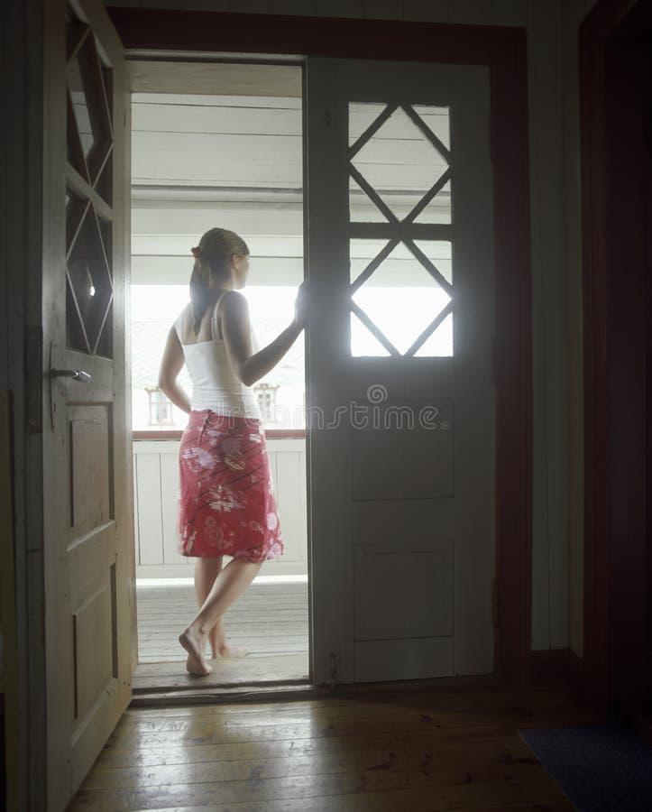 Vrouw die zich in Open Deur bevinden  royalty-vrije stock foto