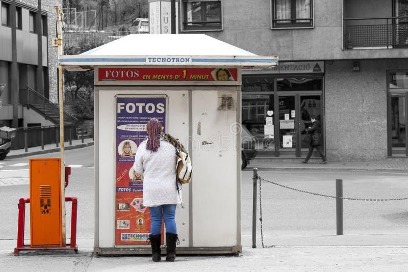 Vrouw die zich voor een machine bevinden om pasfoto's te maken royalty-vrije stock fotografie