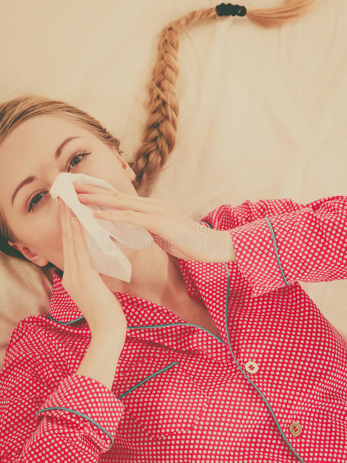 Vrouw die ziek hebbend griep die op bed liggen zijn stock fotografie