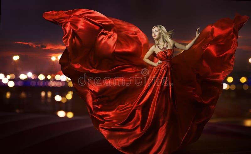 Vrouw die in zijdekleding dansen, het artistieke rode blazen royalty-vrije stock foto