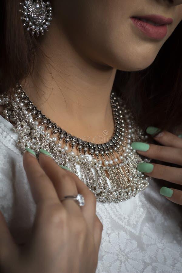 Vrouw die zilveren halsband met vingers het tonen dragen stock foto's