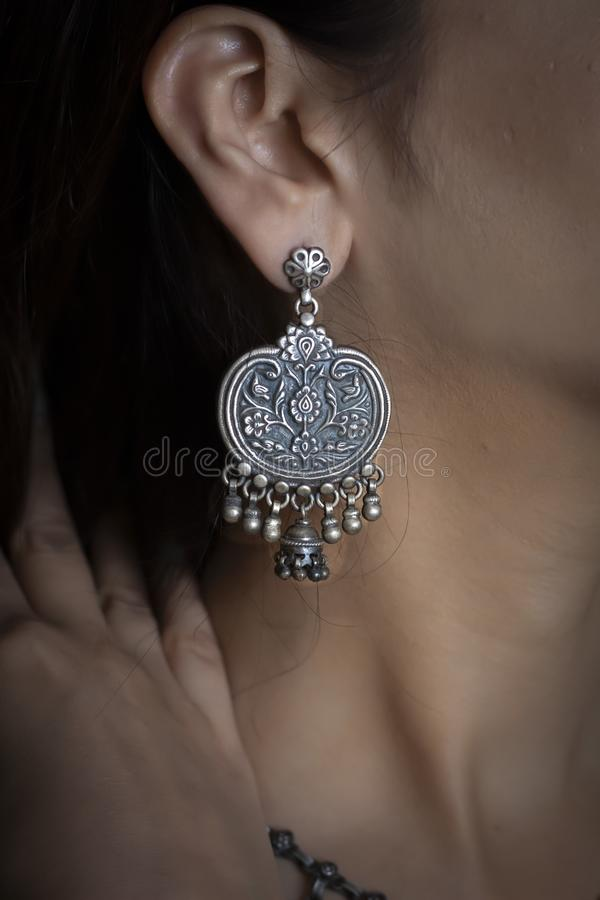Vrouw die zilveren oorring op oor dragen stock afbeeldingen