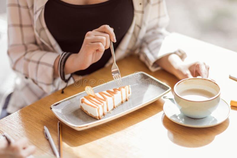 Vrouw die zoet dessert eten terwijl het zitten in koffie, koffiepauze stock afbeelding