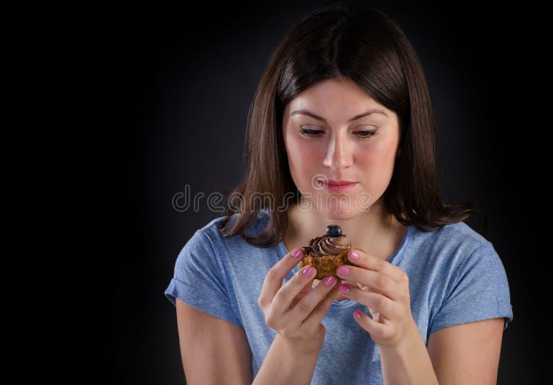 Vrouw die zoete cupcake eten royalty-vrije stock foto