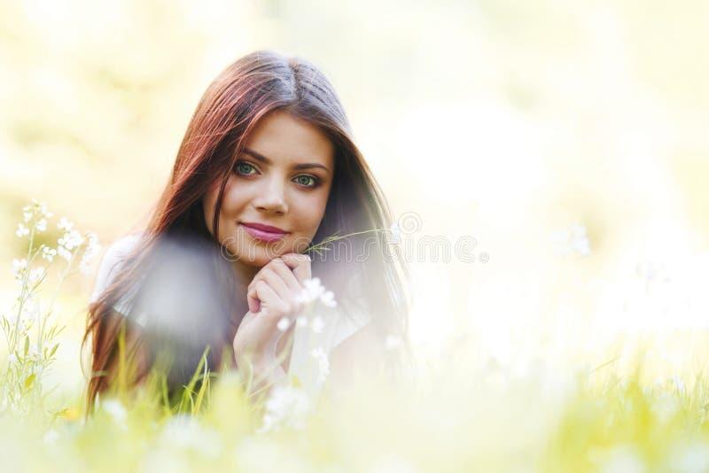 Vrouw die in zonnig de lentepark leggen royalty-vrije stock afbeelding