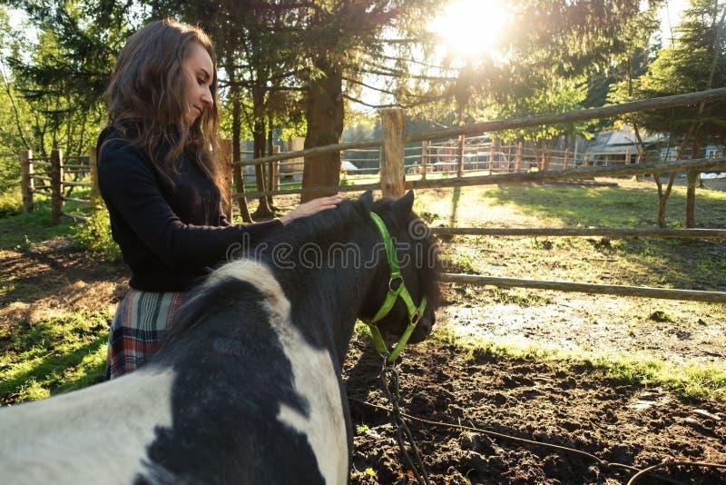 Vrouw die zorg over zwarte poney met lang haar op het gebied nemen royalty-vrije stock foto