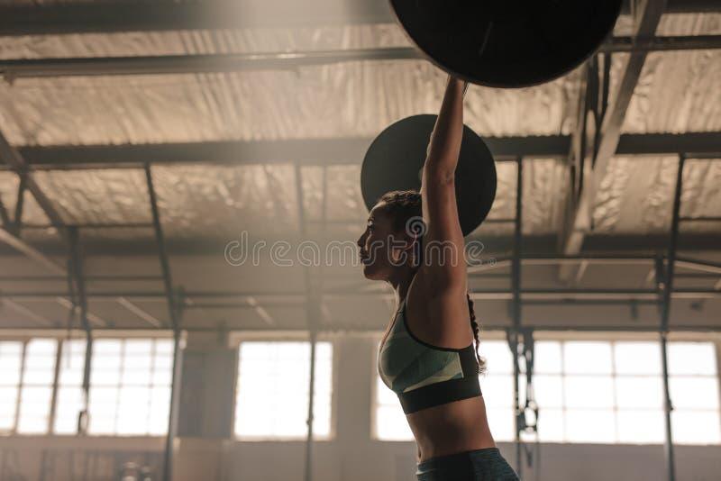 Vrouw die zware gewichten uitoefenen bij gymnastiek stock fotografie