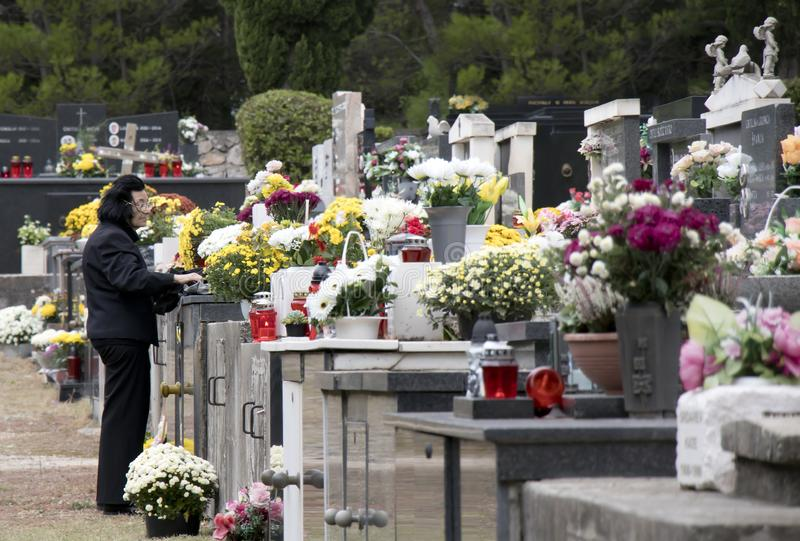 Vrouw die zwarte dragen bij het begraafplaatshoogtepunt van bloemen en candels stock afbeelding