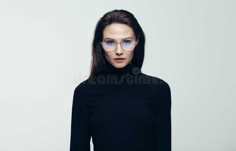 Vrouw die in zwarte kleding bij camera staren royalty-vrije stock foto's