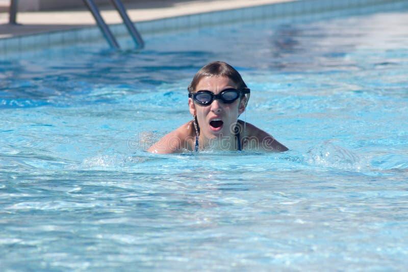 vrouw die in zwembad zwemt stock foto