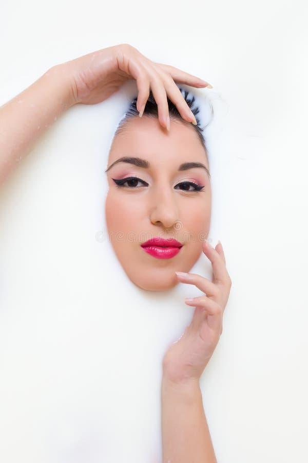 Vrouw diep in melkbad stock afbeelding
