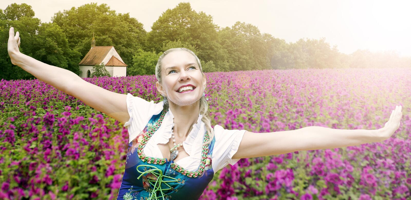 Vrouw in dirndl die haar wapens voor purpere bloem uitspreiden fie royalty-vrije stock fotografie