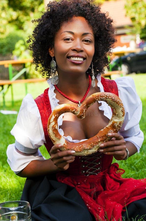 Vrouw in Dirndl met Beierse Pretzl stock afbeeldingen