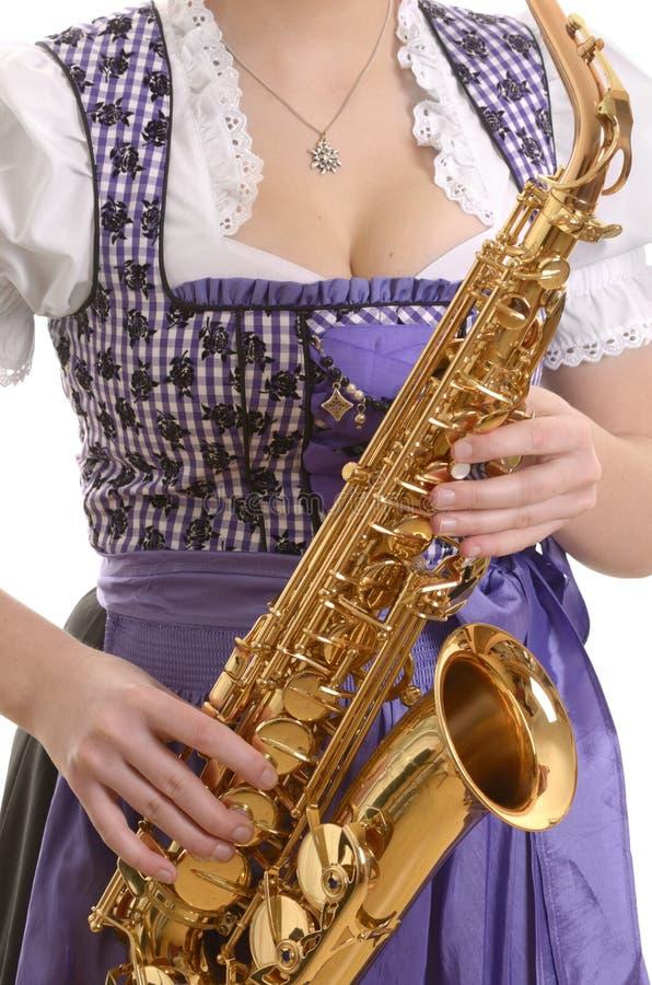 Vrouw in dirndlkleding het spelen saxofoon, detail stock afbeelding