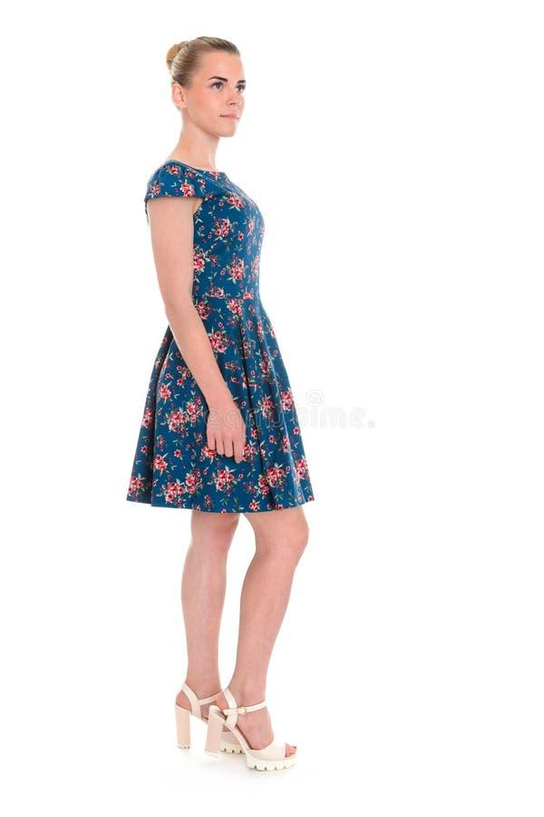 Vrouw in donkerblauwe bloemendiekleding op wit wordt geïsoleerd royalty-vrije stock foto's
