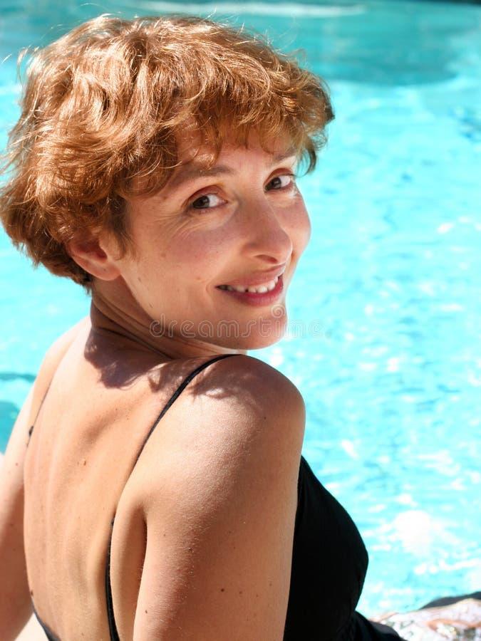 Vrouw door de pool stock fotografie