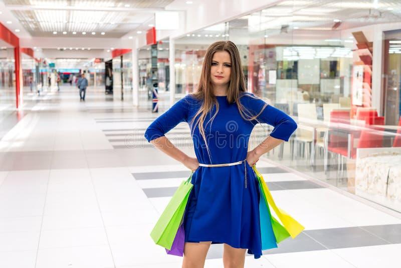 Vrouw door in grote wandelgalerij wordt vermoeid te winkelen die royalty-vrije stock foto