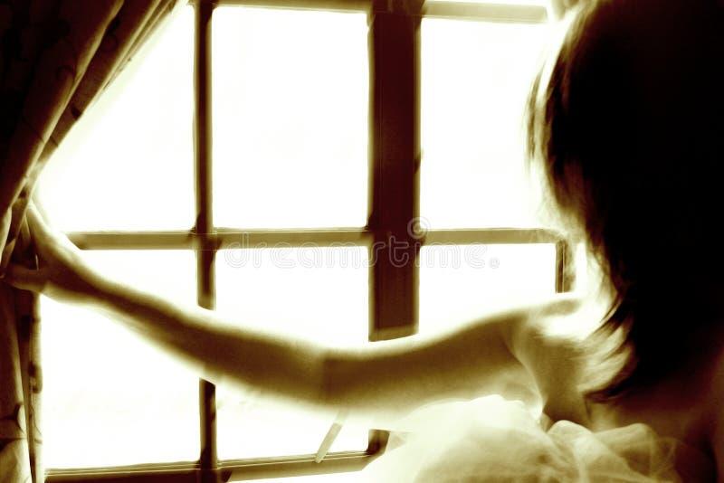 Vrouw door het venster stock fotografie