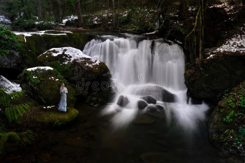 Vrouw door waterval in de winterregenwoud stock afbeelding