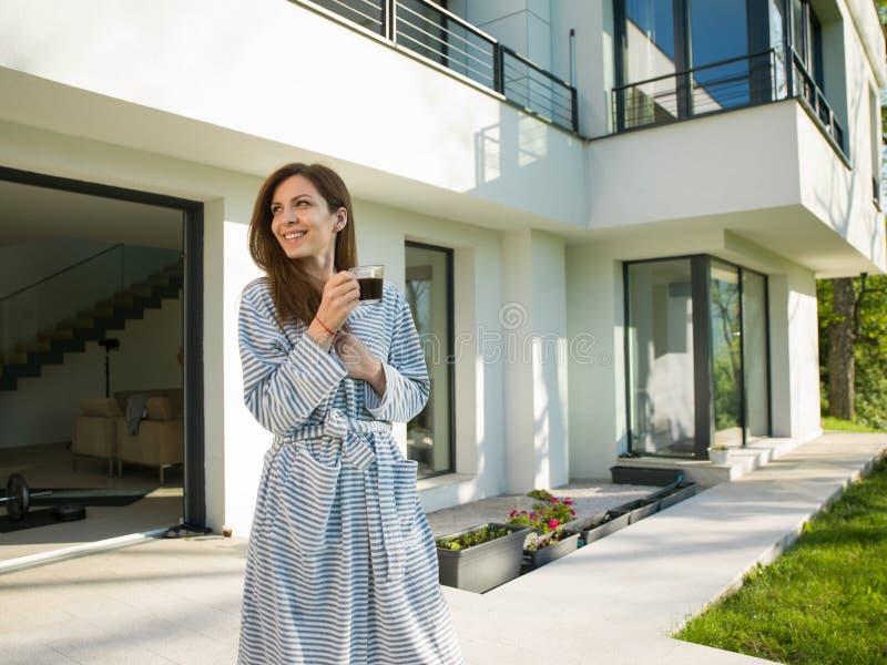 Vrouw in een badjas die ochtend van koffie genieten stock fotografie