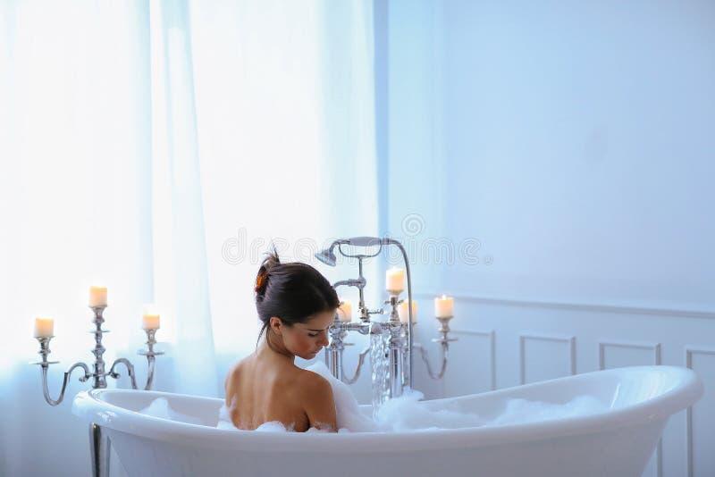 Vrouw in een badkuip stock afbeeldingen