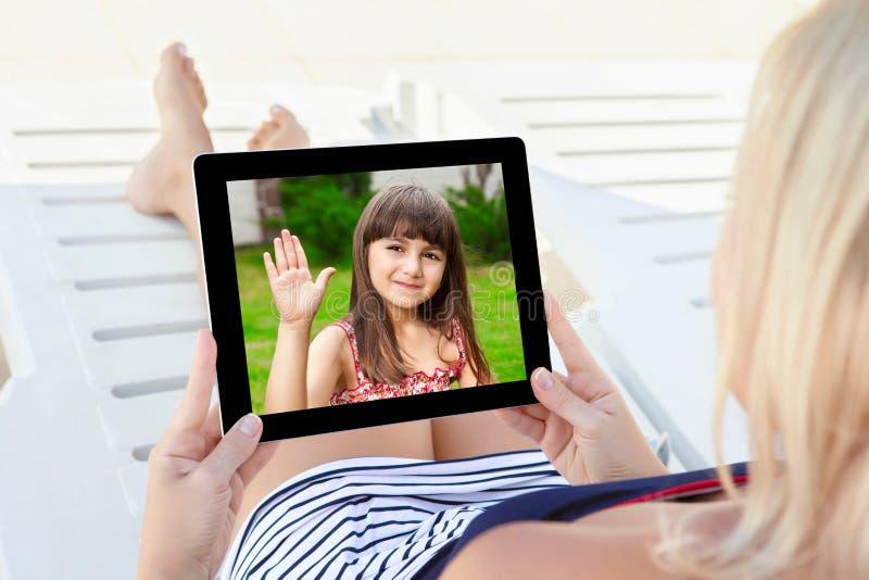 Vrouw in een badpak die op een chaise zitkamer met een tablet a liggen royalty-vrije stock fotografie