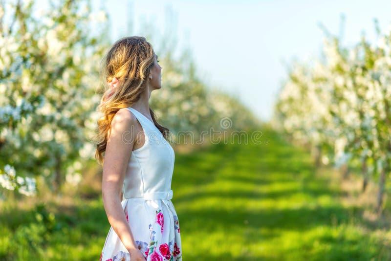 Vrouw in een bloeiende boomgaard bij de lente Het genieten van van zonnige warme dag Retro Stijlkleding Kleurrijke de lentestemmi stock foto