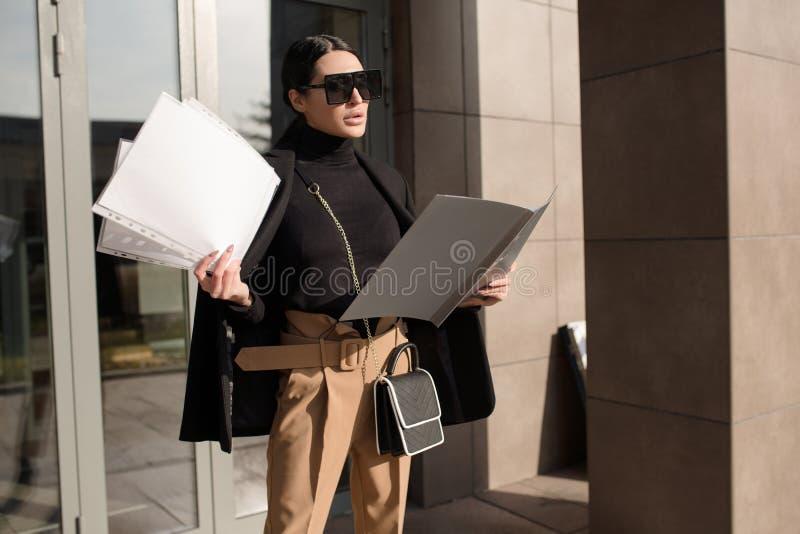 Vrouw in een bril en een bedrijfspak houdt een map in haar handen stock foto's