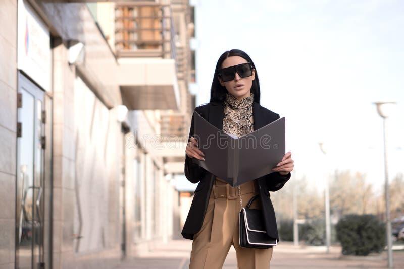 Vrouw in een bril en een bedrijfspak houdt een omslag royalty-vrije stock foto's