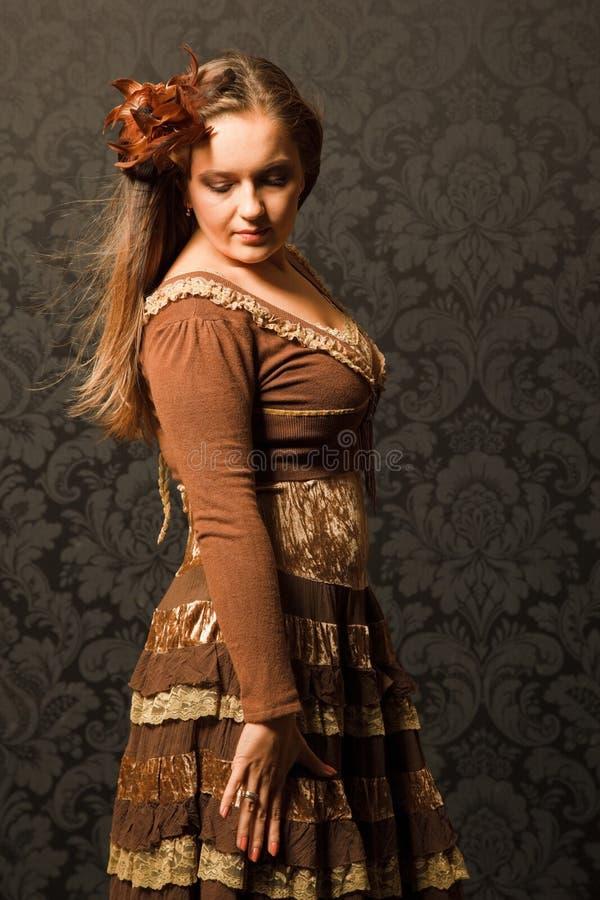 Vrouw in een bruine kleding die zich naast een muur bevindt. stock fotografie