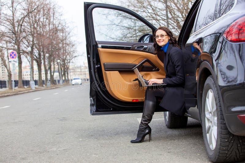 Vrouw in een donkere laagzitting op de drempel van de auto stock foto