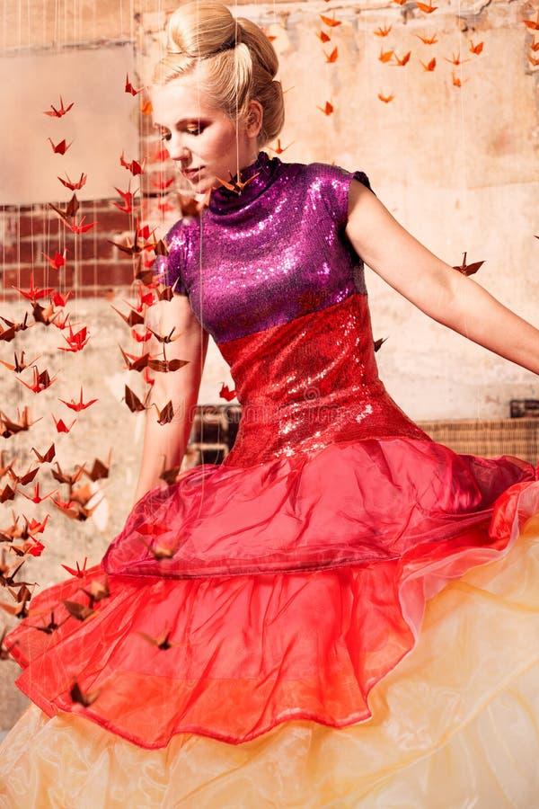 Vrouw in een formele kleding met origamivogels stock afbeelding