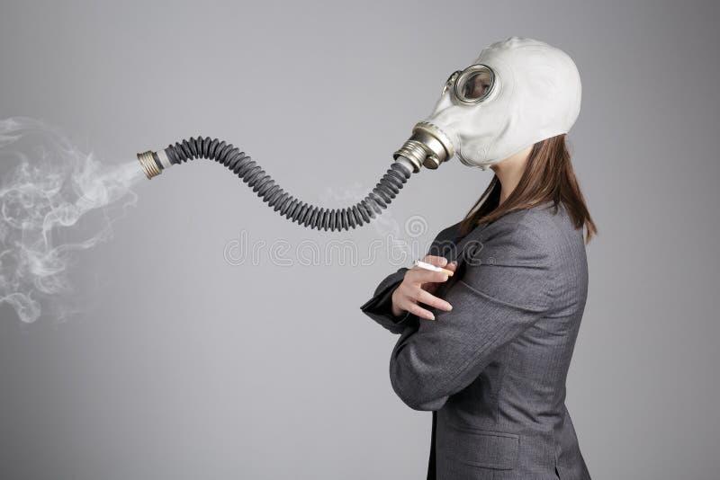 Vrouw in een gasmasker met een sigaret stock afbeelding