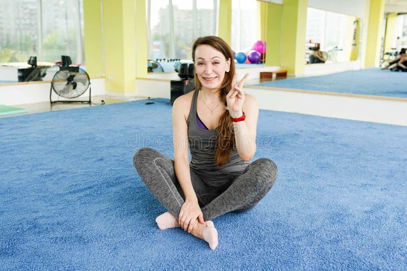 Vrouw in een gymnastiek na geschiktheidsoefeningen, met exemplaarruimte royalty-vrije stock afbeelding