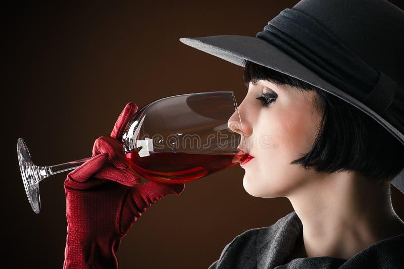 Vrouw in een hoed het drinken wijn stock foto
