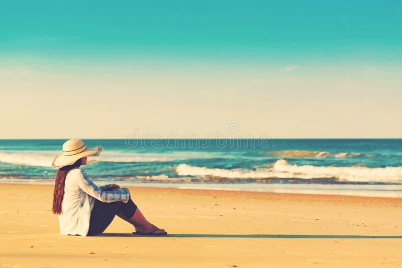 vrouw in een hoedenzitting op het strand royalty-vrije stock fotografie