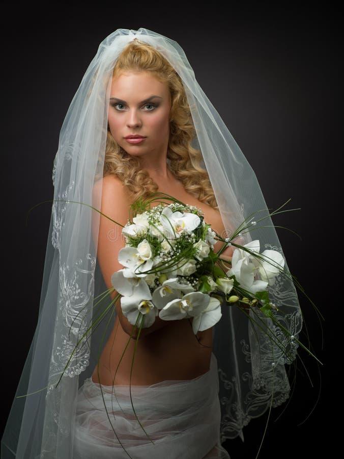 Vrouw in een huwelijkssluier stock foto's