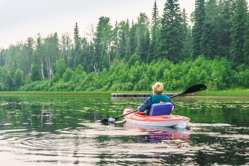 Vrouw in een kajak die langs de meerkust paddelen royalty-vrije stock afbeeldingen