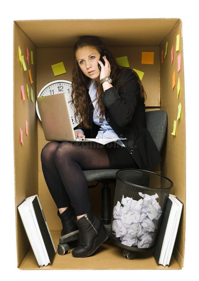 Vrouw in een klein bureau stock afbeelding