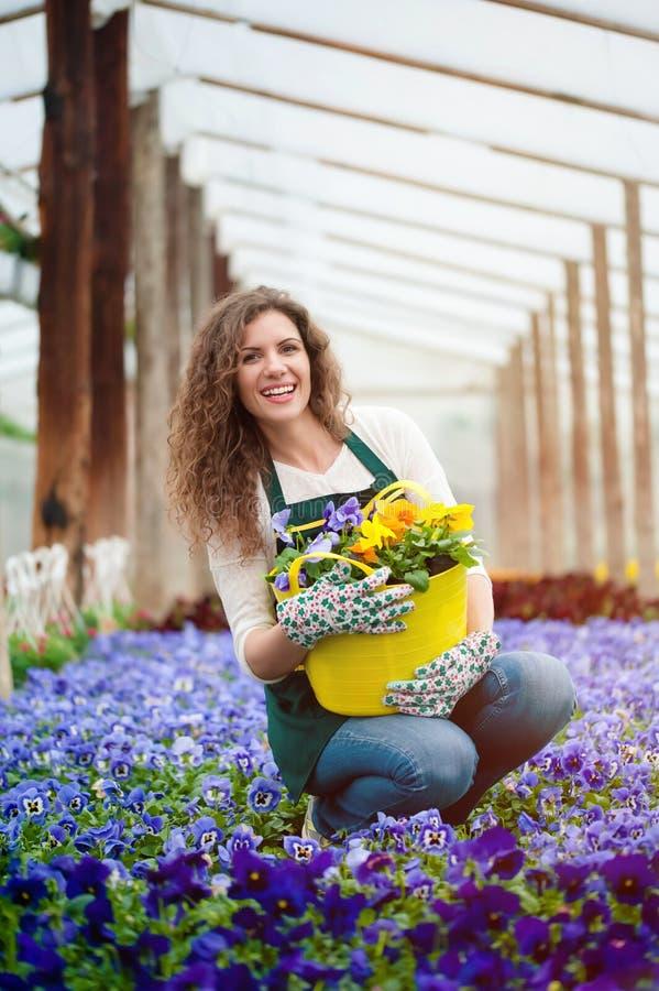 Vrouw in een kleurrijke bloemtuin in een serre royalty-vrije stock foto's